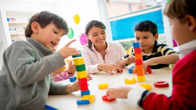Children with ADHD playing with blocks in classroom while teacher looks on as part of school accommodations under IEPS and 504 plans