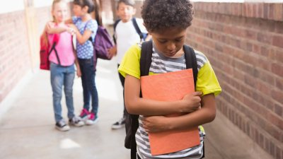 Sad ADHD boy at school being bullied by other kids.