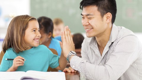 Girl with ADHD high fiving her teacher in classroom