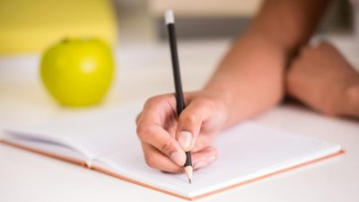 Girl with ADHD writing in notebook with apple beside her trying to prepare for class