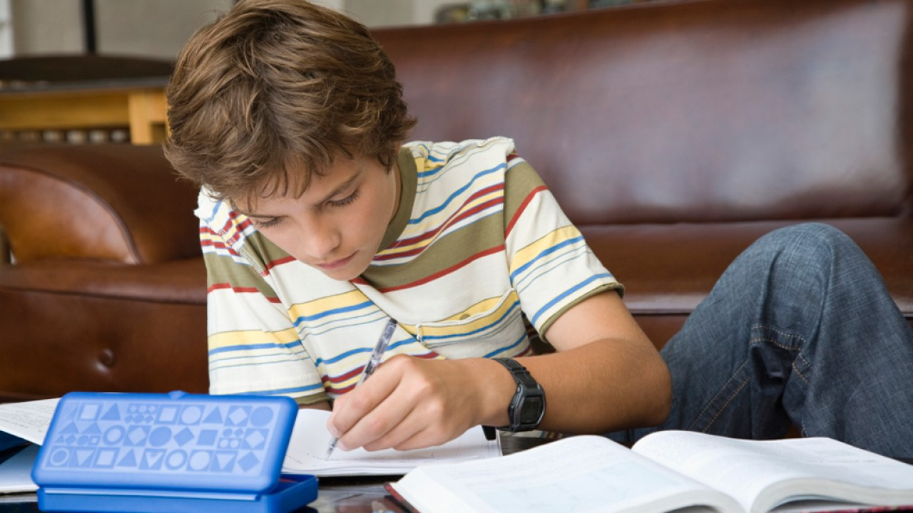 A teenage boy with ADHD doing homework in the living room