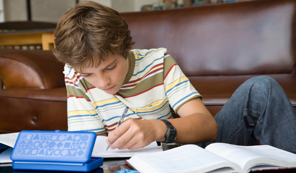 Two kids sitting at a table working on their homework