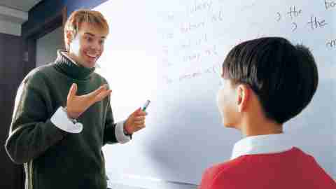 Teacher working with ADHD student in front of white board, enthusiastically explaining lesson plans