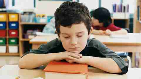 A boy who is both ADHD and gifted resting his head on a book during class