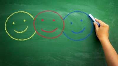 Three smiley faces drawn on blackboard in classroom by student engaged in cooperative learning
