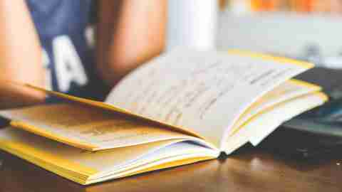 Teen girl with ADHD reading notebook at high school