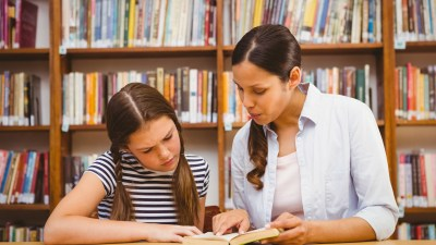 A young girl with ADHD and her tutor working in the library