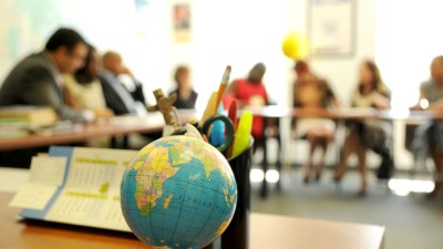 Classroom of ADHD students with tables and globe in focus in foreground