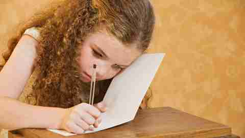 Little girl with curly blond hair and ADHD improving writing skills by working in notebook