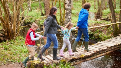 Parents with ADHD children walking across bridge on nature trail hike