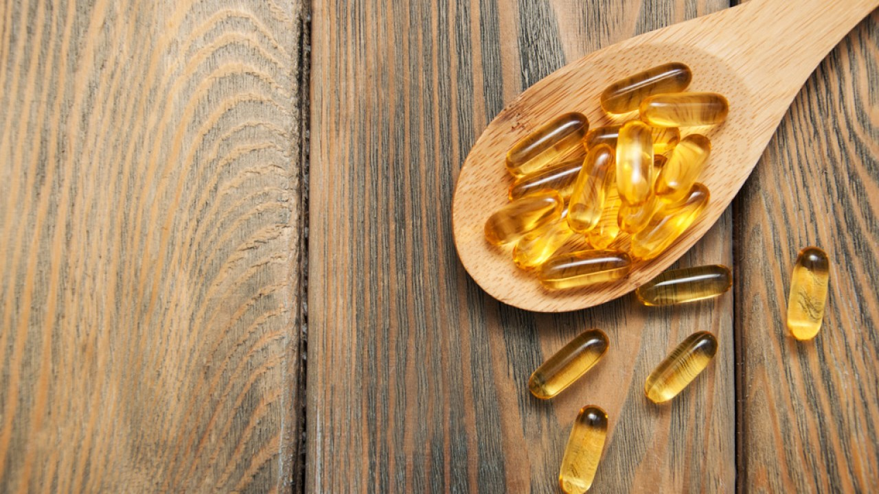 Fish oil capsules in wooden spoon are good for people with ADHD