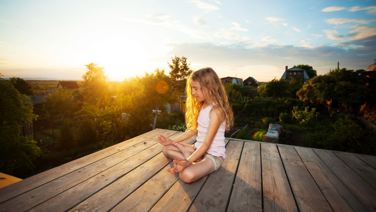 Girl with ADHD meditating outside on porch at sunset.