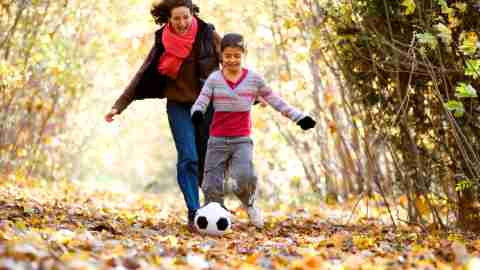 A mother and daughter playing soccer together, demonstrating how physical activity and one-on-one attention can serve as natural remedies for ADHD