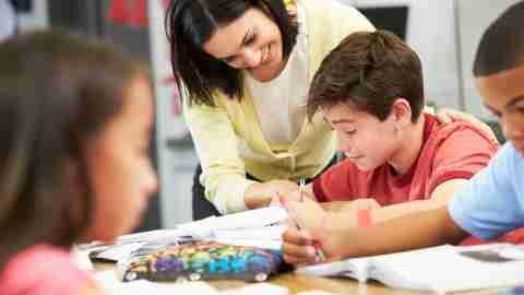 A teacher helping a child focus on his classwork