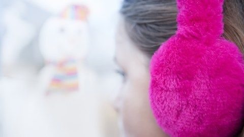 A girl wearing earmuffs to help herself focus