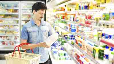 "A man with ADHD puts milk in his basket at the supermarket, while thinking, ""I hate grocery shopping."""