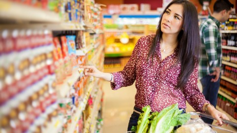 "A woman with ADHD putting food in her cart at the supermarket while thinking, ""I hate grocery shopping."""