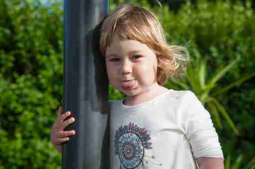 portrait funny expression of ADHD two years old blonde happy smiling child sticking out tongue at garden