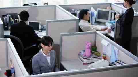 An adult working in a cubicle uses white noise to drown out others and stay on task.
