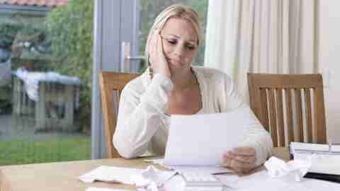 A woman looking at her child's IEP, frustrated with its problems