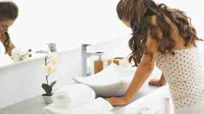 A woman with hypersensitivity stands over a bathroom sink.