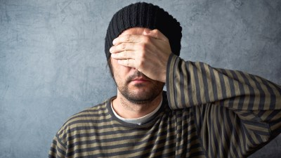 A man with hypersensitivity covers his eyes.