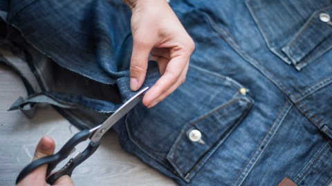 A woman with hypersensitivity cuts the irritating tag out of her pants.
