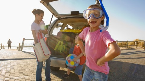 Girl with snorkel by family unpacking van shows her sense of humor.