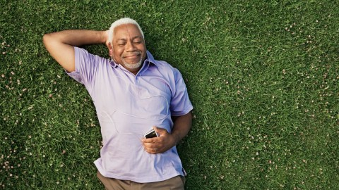 A senior man with ADHD lays in the grass and listens to music.