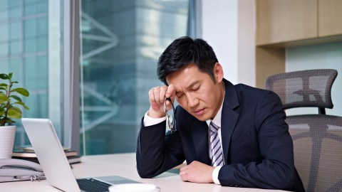 A businessman with ADHD wastes time in his office, resting his forhead on his hand.