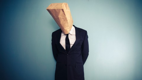An adult with ADHD has a bag over his head, symbolizing the shame that often accompanies ADHD.