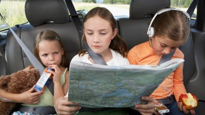 Children entertaining themselves in back seat of a car, following travel tips and packing games