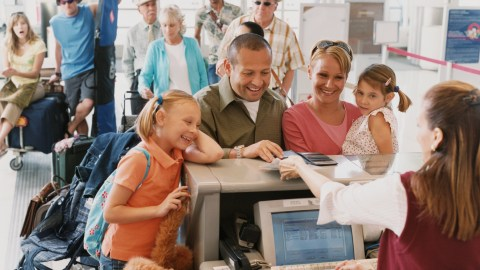 Family checking in for a flight using smart travel tips
