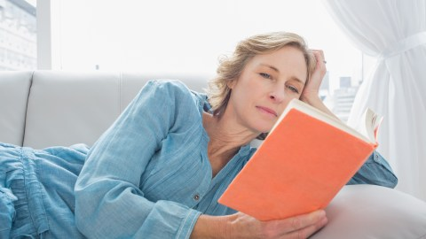 A woman with ADHD relaxes and reads a book on the couch, taking some personal time in her marriage.