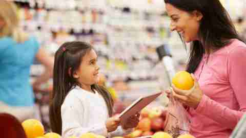 A mother and daughter use a shopping list in the fruit department of the grocery store to help stay on task while shopping.