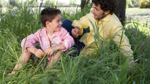 A father sits in the grass under a tree and talks with his son about executive function
