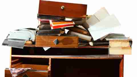 A messy desk, covered in books and drawers. This could cause ADHD stress.