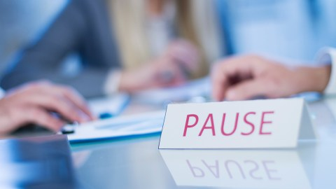 A sign in the center of a conference table full of people that says pause, a reminder to stop periodically to reduce ADHD stress