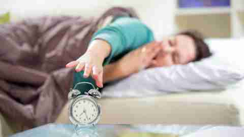 A woman turning off her alarm clock, since proper sleep is a good ADHD coping skill