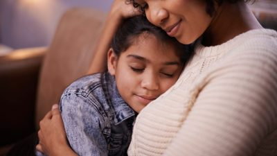 An overwhelmed mom relaxes for a minute to give her daughter a hug.