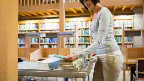 Librarian pushing book cart in college library