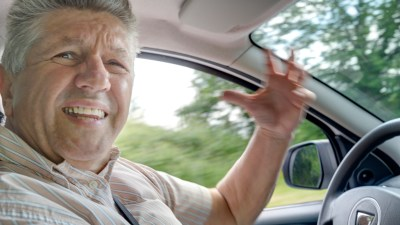 A man driving a car, angry that most people don't know facts about Tourette Syndrome