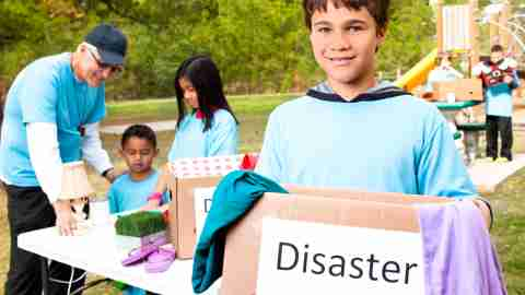 Young boy volunteering over summer, learning about disaster and loss