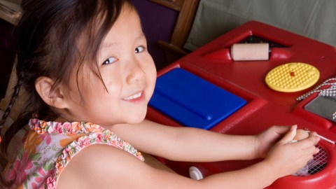 A girl with SPD plays with a sensory table.