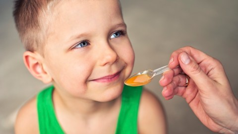 A child taking liquid ADHD medication, which has different side effects than traditional formulations