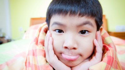 Boy with ADHD in bed with blanket sticking out tongue