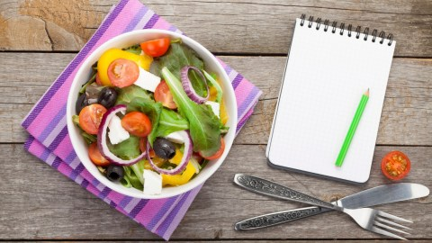 A fresh healthy salad with a blank notepad next to it to track ADHD weight loss goals