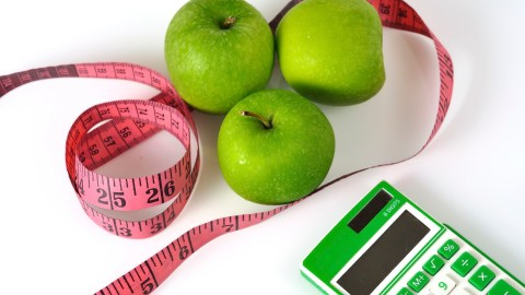 Three apples, a measuring tape, and a calculator, all items to use for ADHD weight loss