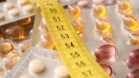 Vitamin supplements and a tape measure, both tools that can help acheive ADHD weight loss