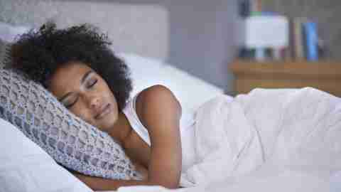 A woman with ADHD asleep in bed. Getting enough sleep is crucial for weight loss.